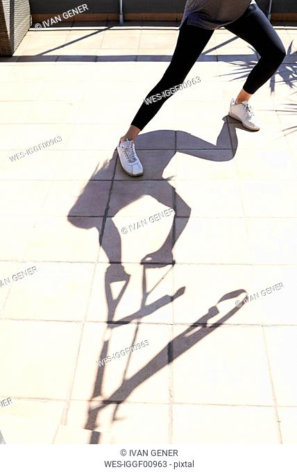 Silhouette shadow of woman doing suspension training on terrace