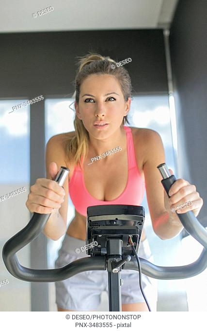 Pretty woman doing spinning bike in fitness center