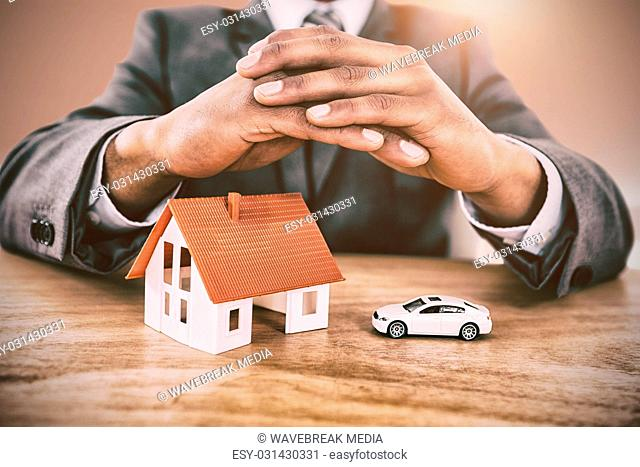 Composite image of businessman protecting house model and car with hands on table