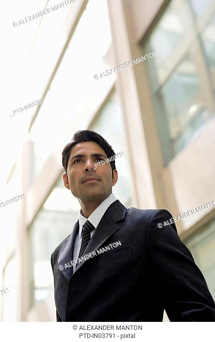 Businessman outside office building looking past camera