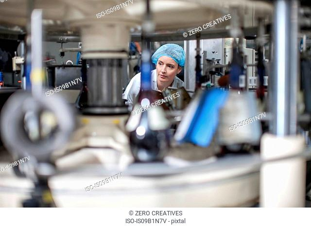 Lab technician checking equipment at packaging factory