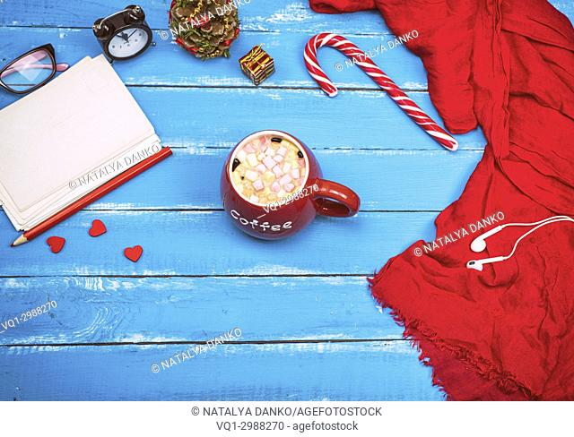 red cup of coffee with marshmallows and a stack of postcards on a blue wooden background