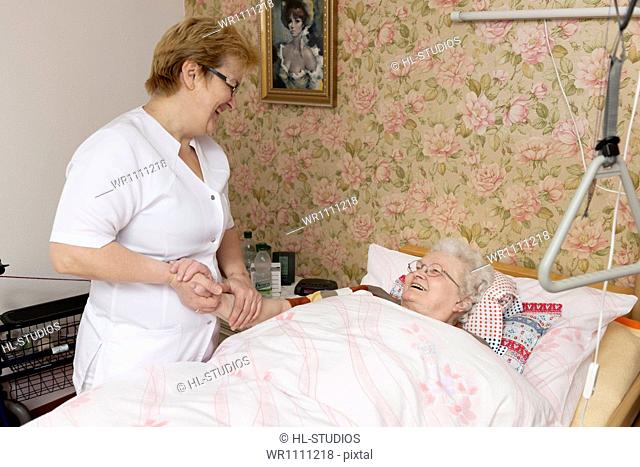 Geriatric nurse talking to old woman in bed