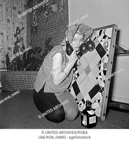 Eine junge Frau lehnt an einem hochgestellten Tisch und nimmt einen Schluck aus einem Glas, Deutschland 1950er Jahre. A young woman leaning on a small table