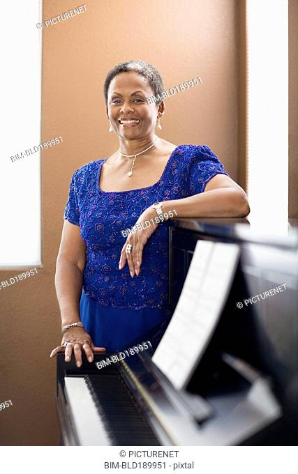 African woman in evening dress leaning on piano