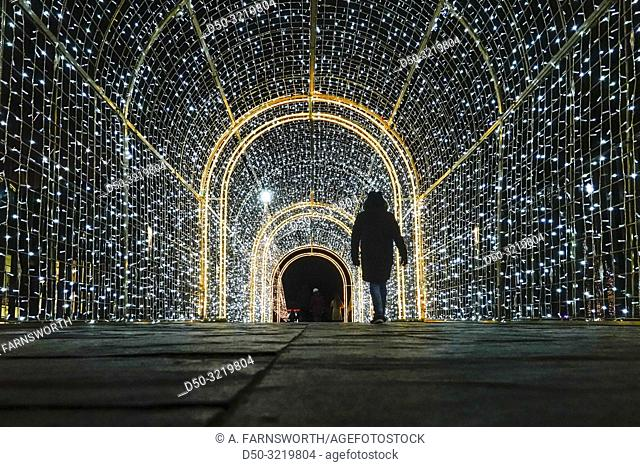 Gdansk, Poland Christmas decorations in a light tunnel at the Forum Mall and pedestrians