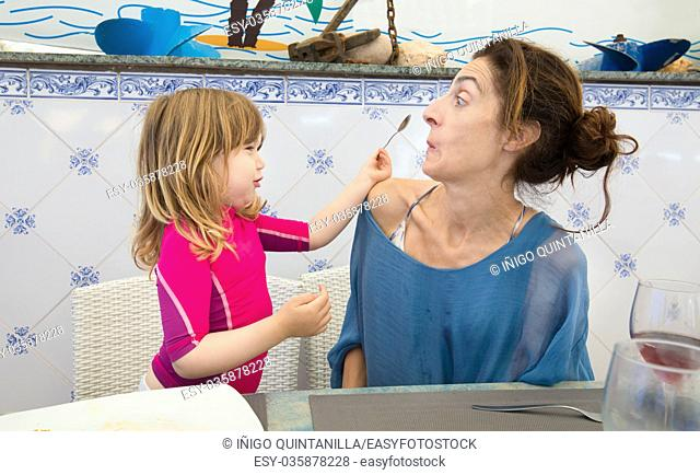 funny scene of three years old blonde child putting spoon in the face of woman mother sitting in restaurant
