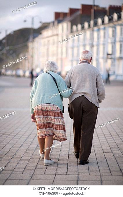 Elderly couple, old man and woman, walking in Aberystwyth promenade, summer evening, Wales UK