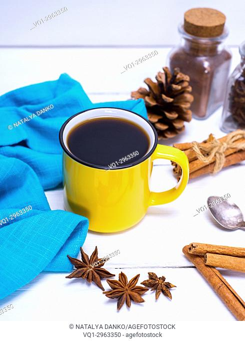 yellow cup with black coffee and cinnamon on a white wooden table, top view