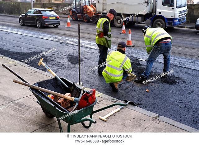 Three workmen repairing the road surface damage with potholes and water erosion, Glasgow, Scotland, UK, Great Britain