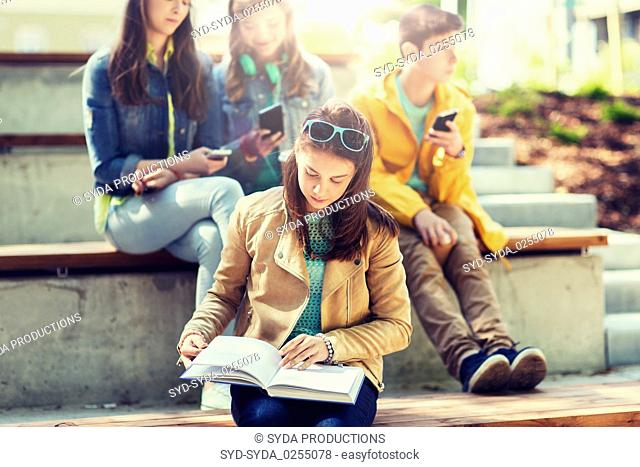 high school student girl reading book outdoors