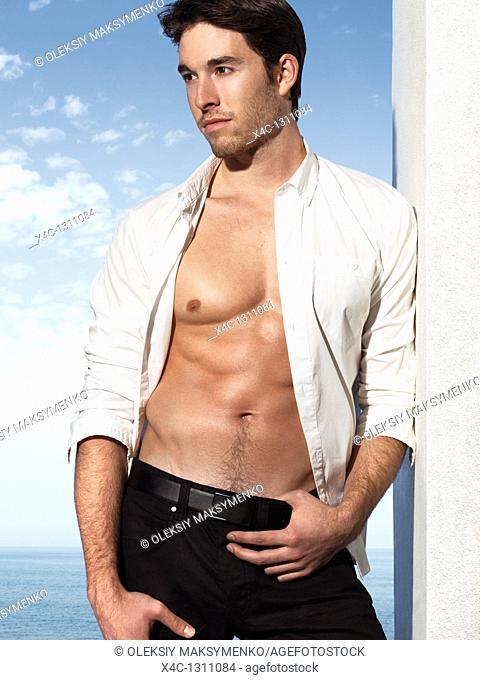 Fashion photo of a young man wearing unbuttoned dress shirt on a sea shore