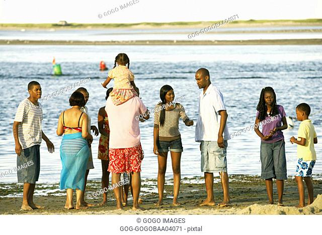Extended African family playing on the beach together