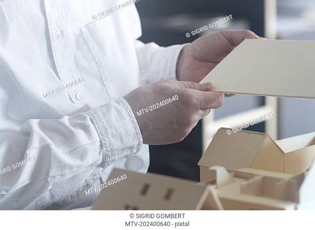 Cropped image of a architect working on model house in the office, Freiburg im Breisgau, Baden-Württemberg, Germany