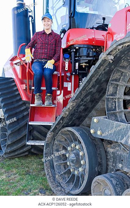 farm girl on a Quadtrac tractor, near Dugald, Manitoba, Canada