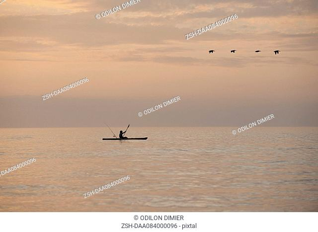 Person kayaking at sunset