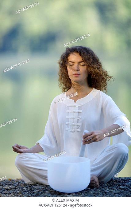 Beautiful young woman in white silk clothes meditating with a quartz crystal singing bowl, healing sound therapy, in the morning sunrise by the lake in the...