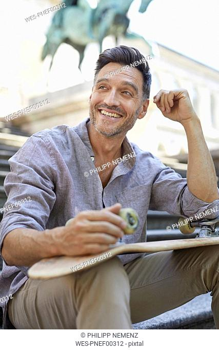 Portrait of laughing mature man with skateboard sitting on stairs