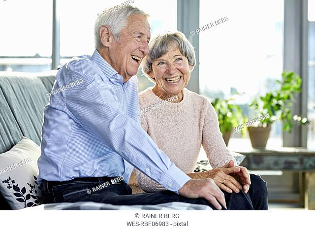 Portrait of laughing senior couple sitting together on couch