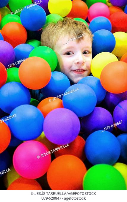 Child playing with colorful plastic balls