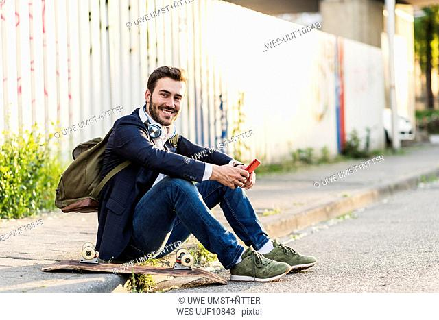 Smiling young man sitting on pavement holding cell phone