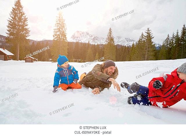 Young man and sons having snowball fight in winter, Elmau, Bavaria, Germany