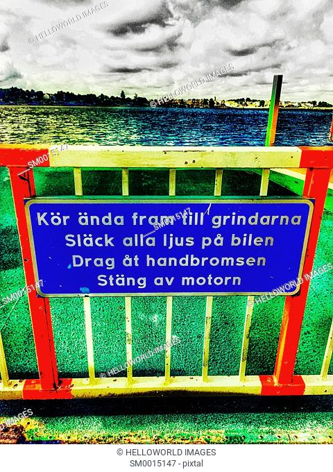 Information sign in Swedish for drivers on ferry saying 'drive all the way to the gate, turn off all the vehicle's lights, engage the handbrake