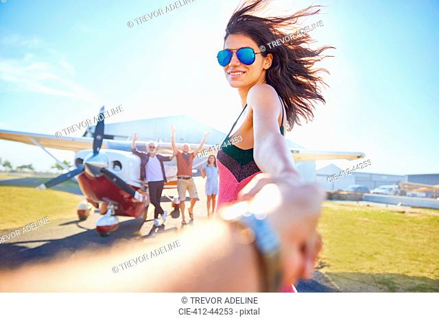 Personal perspective woman leading man by the hand toward prop airplane
