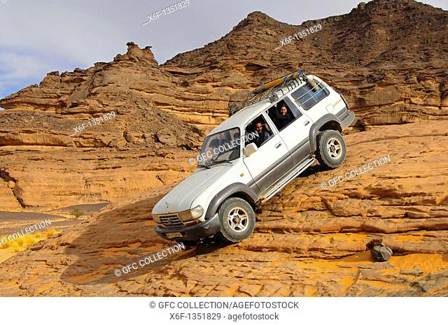 Off-road vehicle with tourists on board traversing a steep rock passage, Acacus Mountains, Sahara desert, Libya