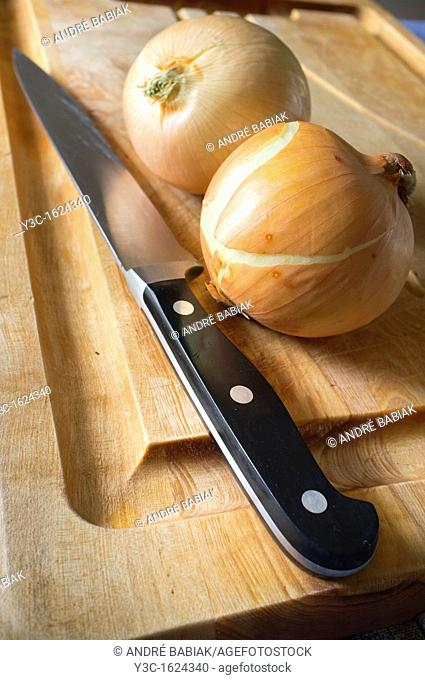 Two onion and knife on a cutting board