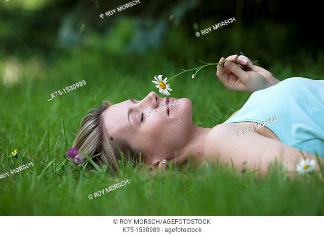 Woman lying on lawn smelling a daisy