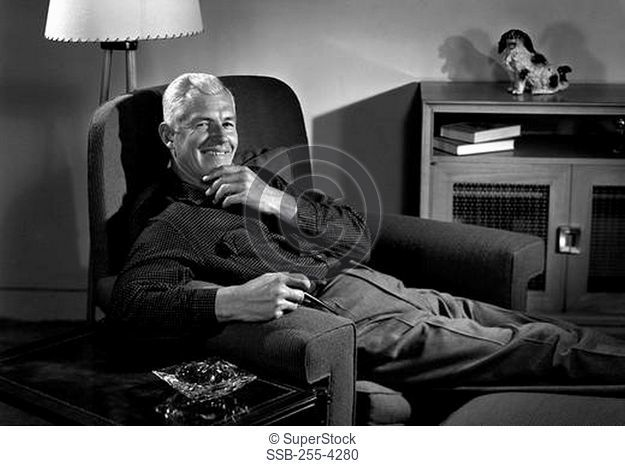 Senior man holding pipe and lying in armchair, portrait