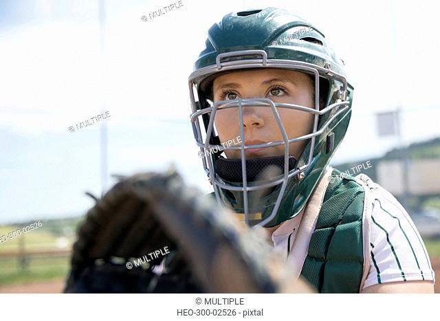 Focused middle school girl softball catcher wearing helmet