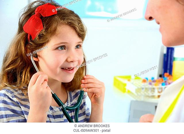Girl listening to doctor's chest using stethoscope smiling
