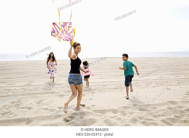 Family flying kite on sunny beach