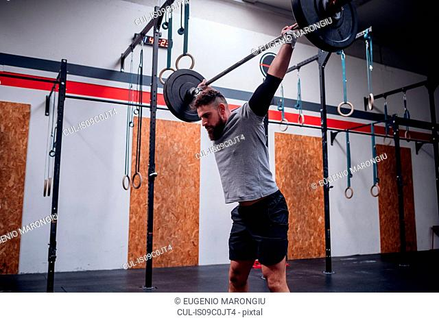 Young man lifting barbell in gym