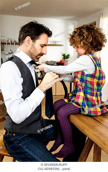 Girl tying father's tie in kitchen