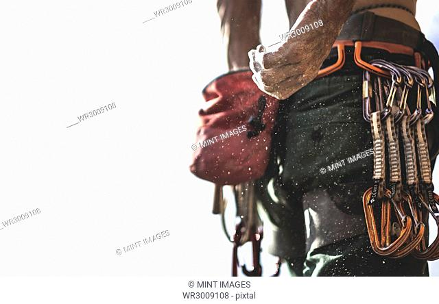 Close up of a mountaineer reaching back to a pouch of chalk on his belt