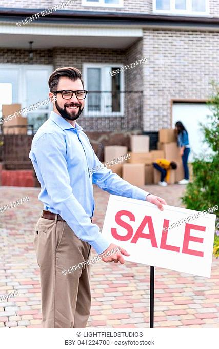 young realtor with sale signboard in front of house with people moving out