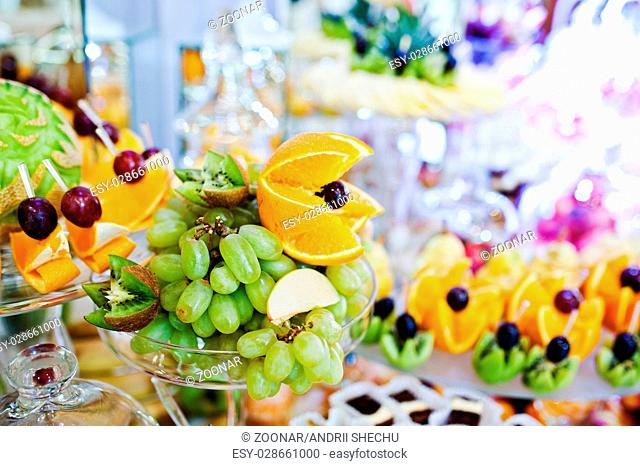 Elegance wedding reception table with food and decor. White grape, orange and other fruits