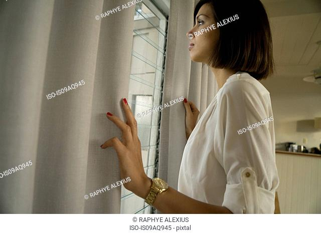 Mid adult woman gazing out of curtained window