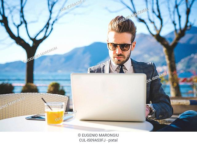 Businessman using laptop at lakeside cafe, Rovato, Brescia, Italy