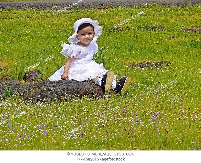 Small girl seating at green heaths, Plateau of flowers, Kaas, Satara, Maharashtra, India