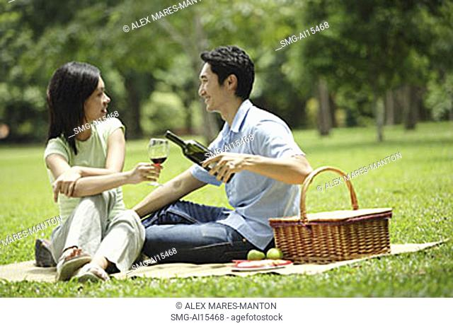 Couple in park, man pouring wine for woman, portrait