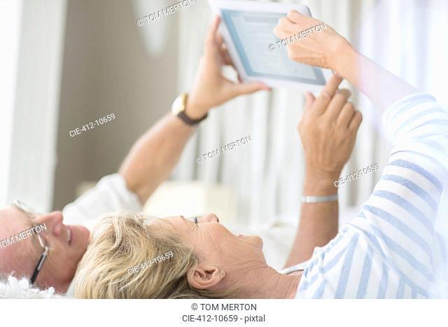 Older couple using digital tablet on bed