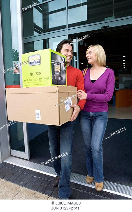 Young couple leaving shop with boxes, smiling at each other, low angle view