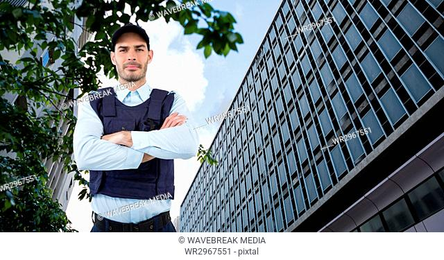 Portrait of confident security guard with arms crossed standing against building in city
