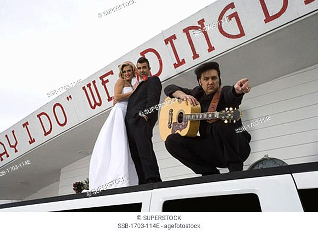 Low angle view of a bride and groom standing on a limousine with a mature man at a drive-thru wedding chapel