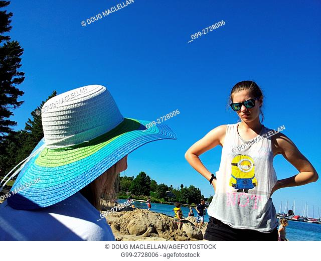 Teenage daughter in a tee-shirt looking at her mother who is wearing a blue and white straw hat while on vacation on a beach on Georgian Bay, Lion's Head