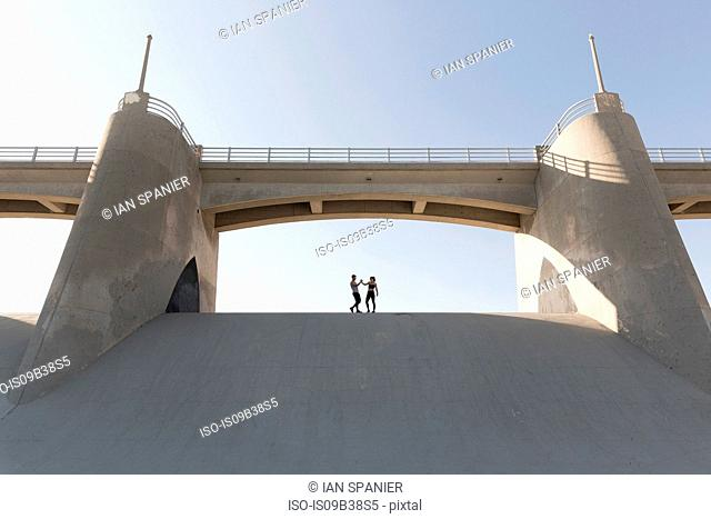 Couple holding hands under bridge, Van Nuys, California, USA